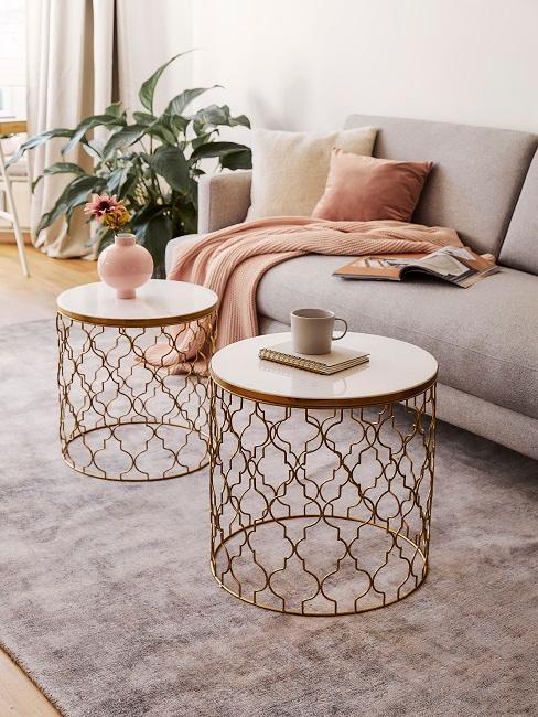 Zwei Couchtisch ein Gold mit Deko auf grauem Teppich vor Sofa