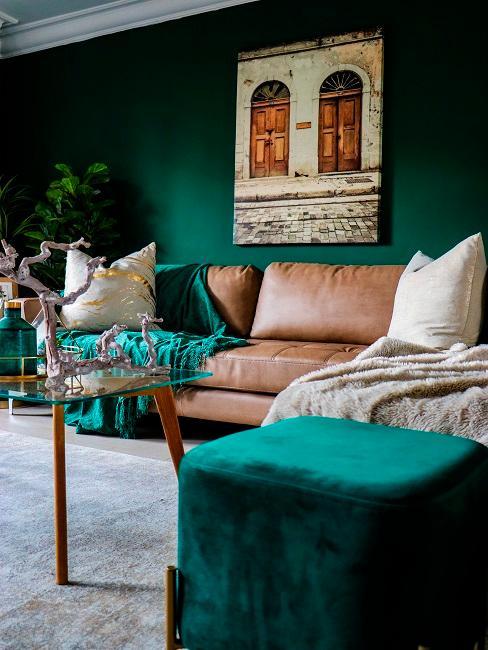 Dunkelgrüne Wand in Wohnzimmer mit brauner Couch und dunkelgrünen Accessoires