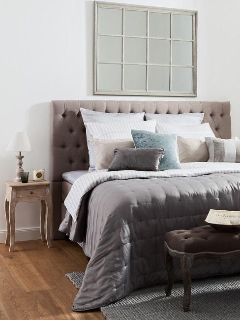 Schlafzimmer im Landhausstil mit braunem Polsterbett und kleinem Nachttisch