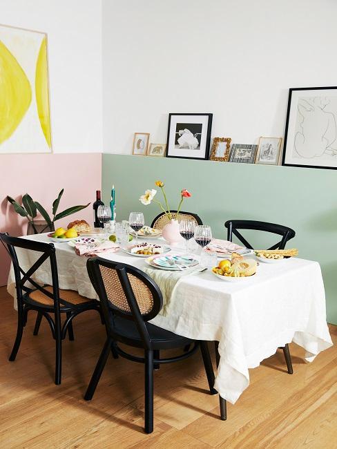 Esszimmer mit pastellfarbenen Wänden, schwarzen Stühlen und Bilderdekoration