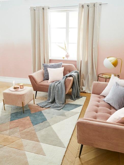 Wohnzimmer mit Altrosa Wandfarbe, rosa Sessel und Sofa, Teppich, Kissen und Decke in Weiß und Grau