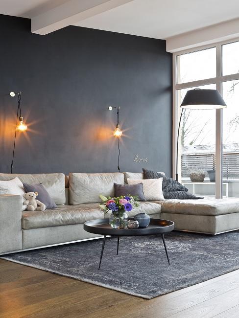 Schwarze Wandfarbe im Wohnzimmer mit beigen Sofa, dunklem Teppich und Wandleuchten