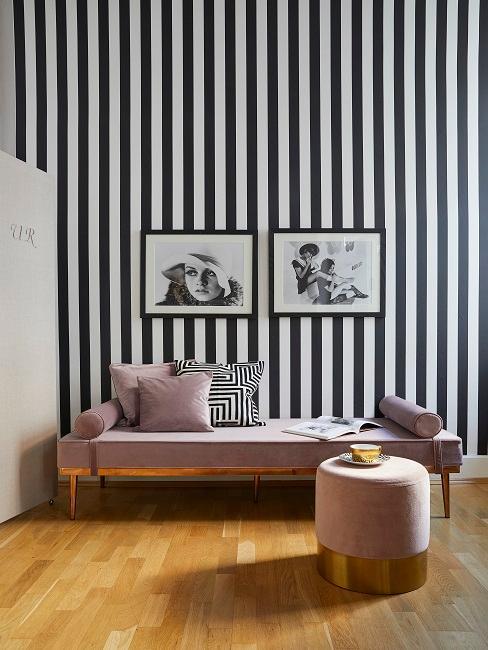 Schwarz-weiß gestreifte Wand mit Bildern und rosa Liege