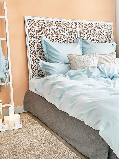 Helle Wandfarbe in Apricot im Schlafzimmer mit weißem Bett und hellblauer Bettwäsche