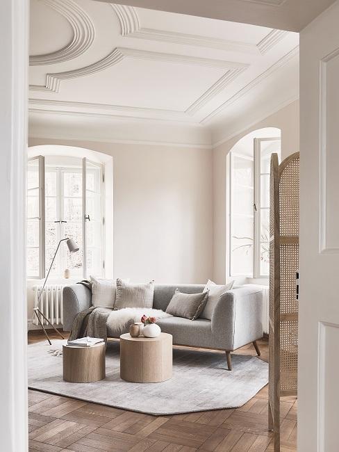 Helle Wandfarbe Beige im Wohnzimmer mit grauem Sofa und Teppich und Holztischen