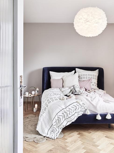 Helle Wandfarbe Beige in Schlafzimmer mit dunkelblauem Bett und weißer Bettwäsche