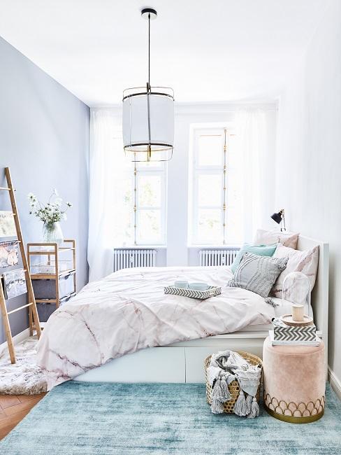 Hellblaue Wand im Schlafzimmer mit weißer Bettwäsche, blauem Teppich und rosa Pouf
