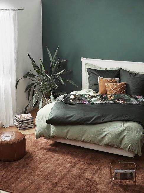 Dunkle Wandfarbe Grün im Schlafuimmer mit grüner Bettwäsche, braunem Teppich und Pflanzen