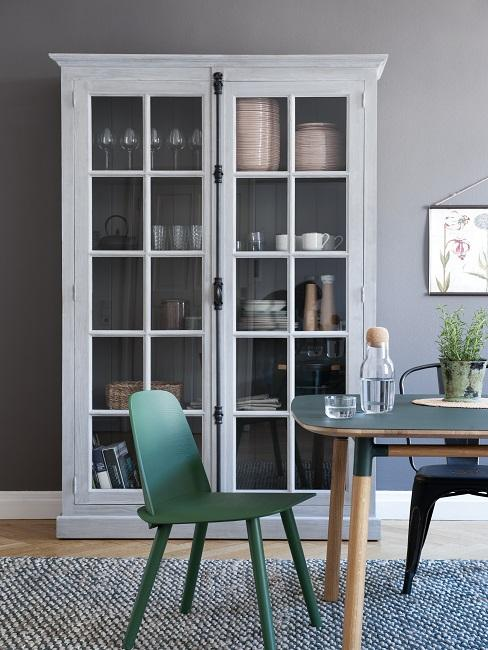 Weißer Vitrinenschrank mit grünen Stühlen und schwarzem Holztisch