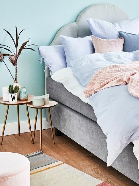Wandfarbe Türkis im Schlafzimmer mit grauem Bett, goldenen Beistelltischen und hellblauer Bettwäsche