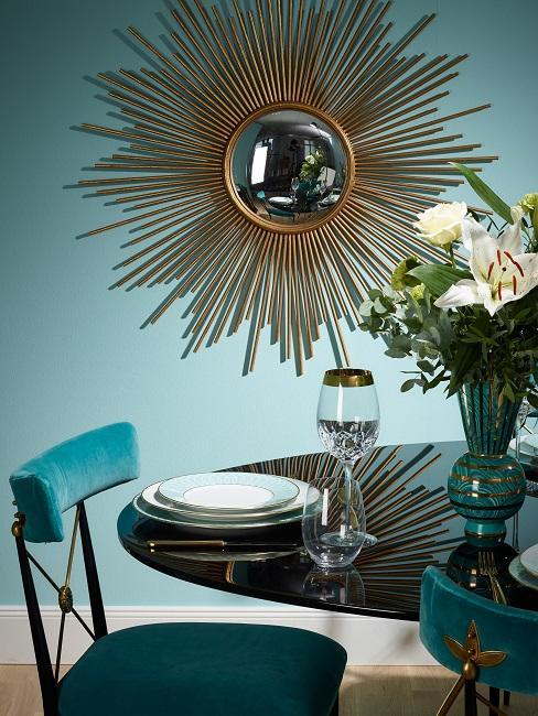 Esszimmer mit goldenem Sonnenspiegel, schwarzen Glanztisch mit Tischdeko, Vase und Samtstühlen in Türkisblau
