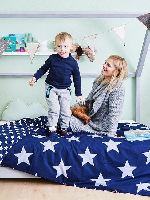 Kind mit Frau auf Bett mit blauer Bettwäsche mit Sternen