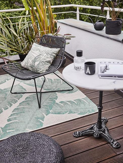 Balkon mit Teppich, Stuhl mit Kissen und rundem Tisch