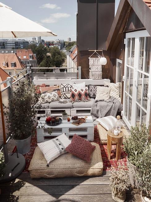 Schöner Balkon im Ethno Stil mit Palettensofa mit Dekokissen, Pouf und Teppich