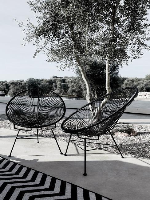 Zwei schwarze Acapulco Chairs auf Terrasse im Freien