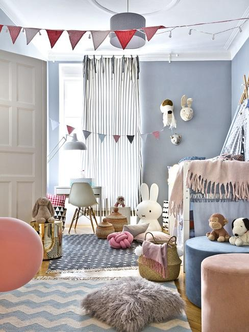 Blaues Spielzimmer mit Spielsachen, Teppichen und Sitzpoufs