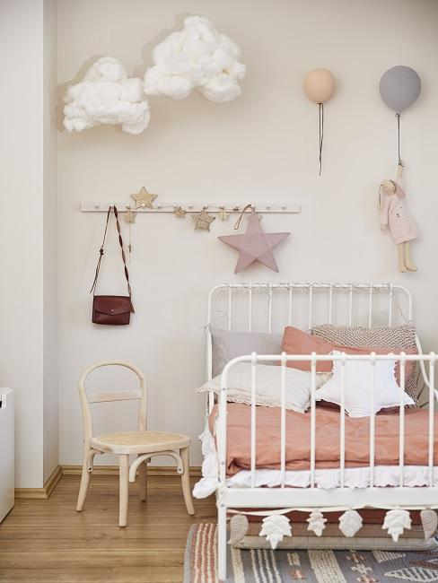 Rosafarbene Bettwäsche mit Kissen und bunter Wanddeko im Kinderzimmer