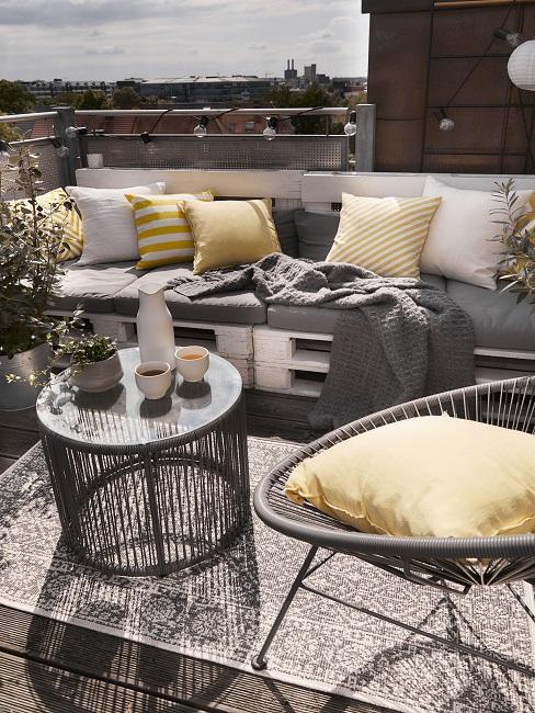 Balkon mit Pallettensofa mit gelben Kissen, Sessel, Outdoor Teppich und Beistelltisch