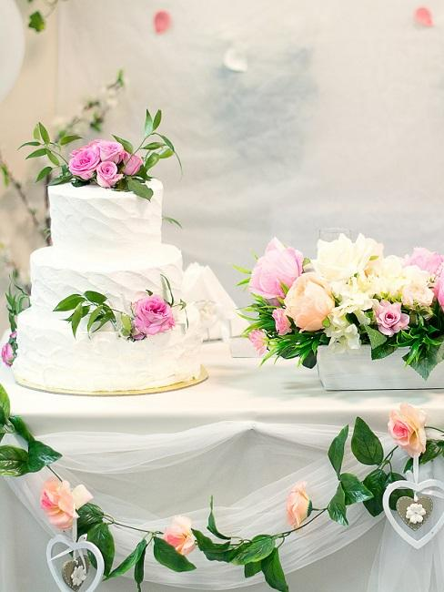 Hochzeitskuchen auf Tisch mit Bluemngirlanden