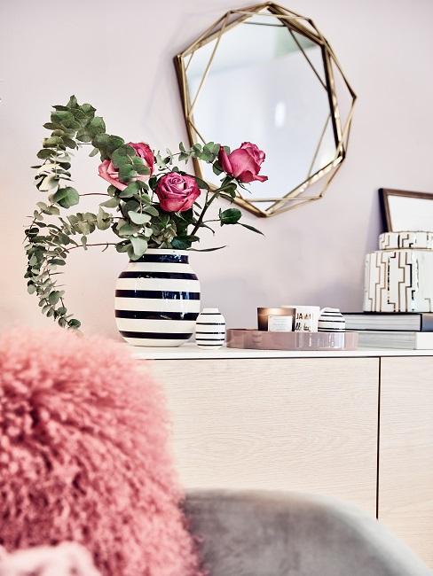 Pinke Rosen in gestreifter Vase auf Konsole