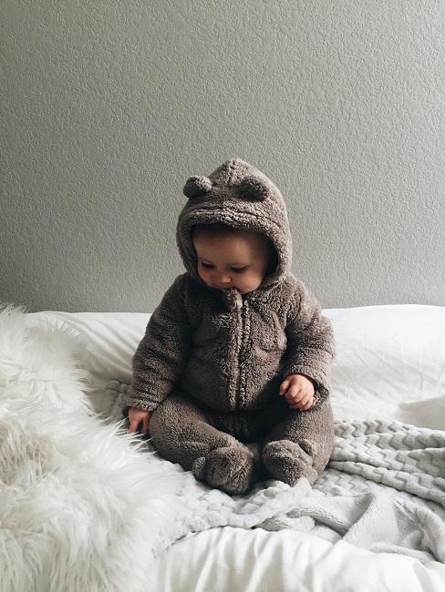 Baby sitz auf weißem Bett vor dunkelgrauer Wandfarbe