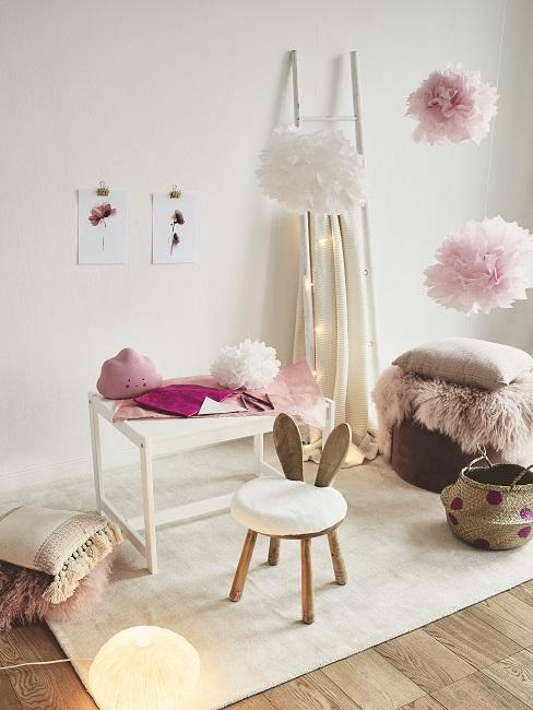 Weißer Kindertisch auf Teppich neben Hasen-Stuhl und Wolkendeko