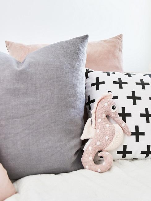 Graue, weiße und rosafarbene Dekokissen