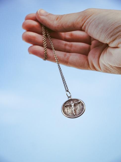 Hand mit Taufkette