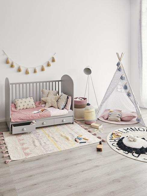 Modernes Kinderzimmer mit Tipi, rosa und gelben Textilien, Girlande und Stehlampe