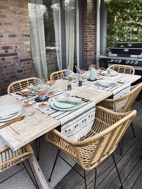 Gedeckter Holztisch mit Stühlen aus Rattan auf der Terrasse