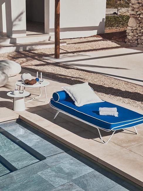 Blaues Daybed mit weißem Kissen am Pool