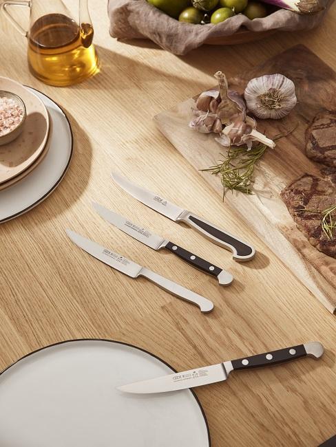 Drei kleine Küchenmesser auf Kochplatte neben Öl und Teller