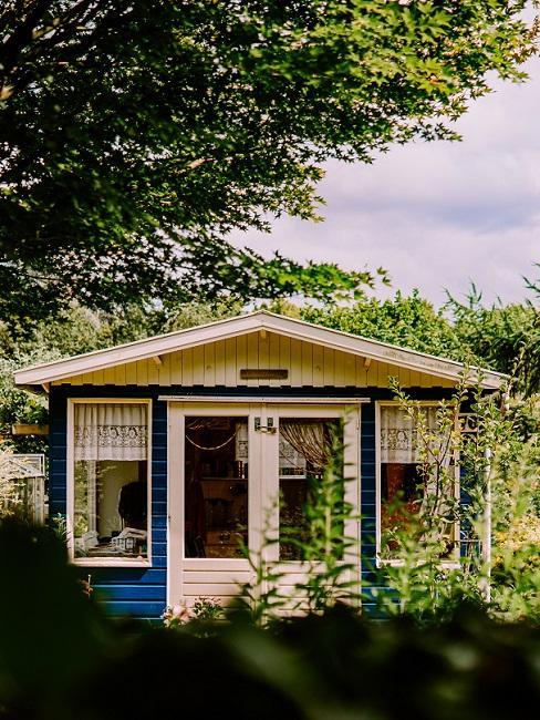 Gartenhaus mit blauer Fassade und Vorhängen aus weißer Spitze
