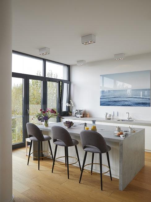 Offene Wohnküche mit Betonplatte und drei grauen Samtstühlen