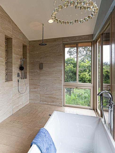 Ebenerdige Dusche mit braunen Fliesen und Badewanne