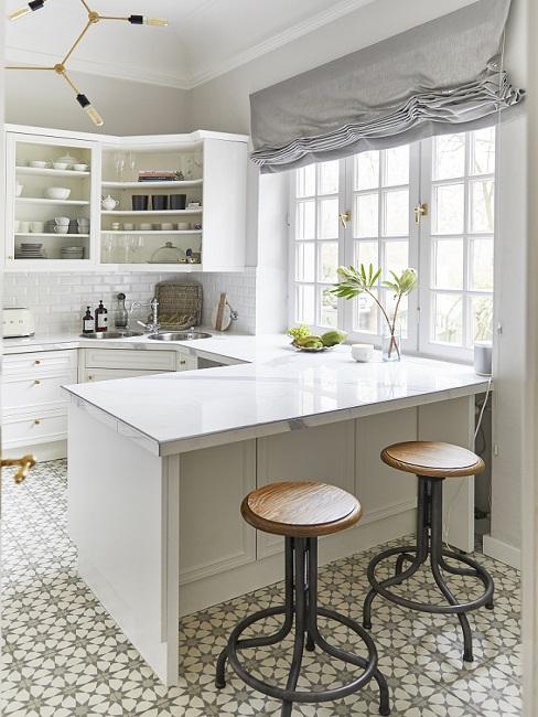 Weiße Küche mit Küchentresen als verlängerte Arbeitsplatte und Barhockern