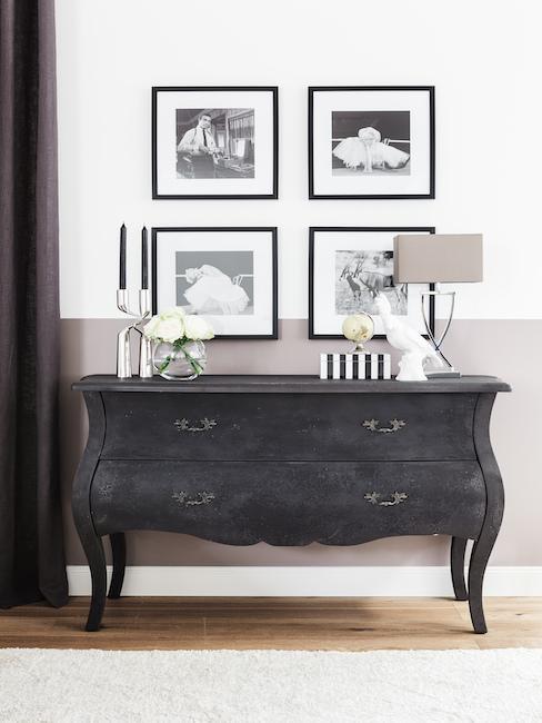 Cómoda de madera oscura en un pasillo con velas y una lámpara encima, y en la pared cuatro fotos enmarcadas en fondo blanco