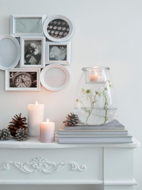 Cómoda en la sala de estar con cadros en blanco y negro, velas rosas y jarrón de cristal con plantas