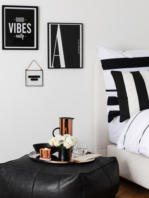 Dormitorio en blanco y negro, cuadros negros, ropa de cama negra y flores