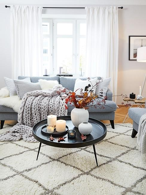 salón escandinavo con una alfombra blanca con estampado,. una mesa central negra con jarrones decorativos, sofá azul con cojines de colores y una manta gruesa de color gris