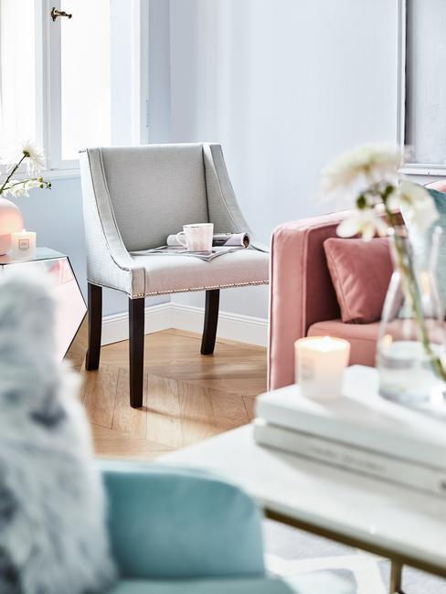 Sala de estar con sillón azul cielo y muebles en gris y rosa