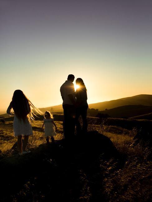 Familia con dos niños en un campo al atardecer