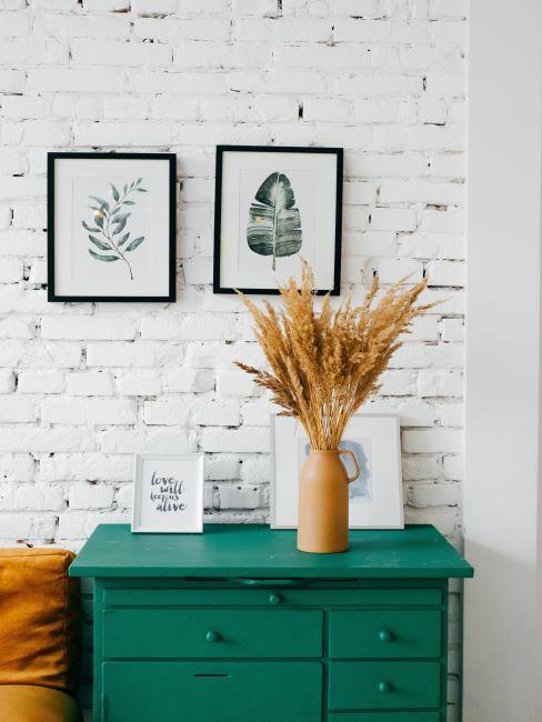 mur de briques peint en blanc, style rustique, minimaliste, avec une commode verte posee devant ce mur, cadres blancs, vase avec fleurs sechees