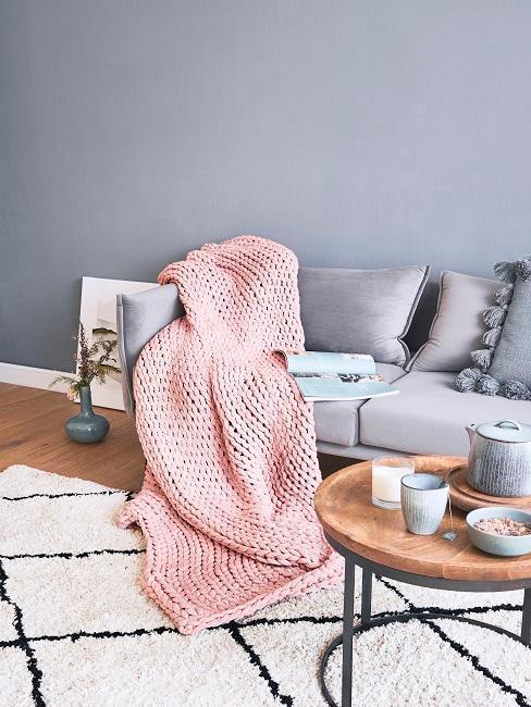 coin séjour avec canapé gris , avec un plaid rose à grosse maille posé dessus