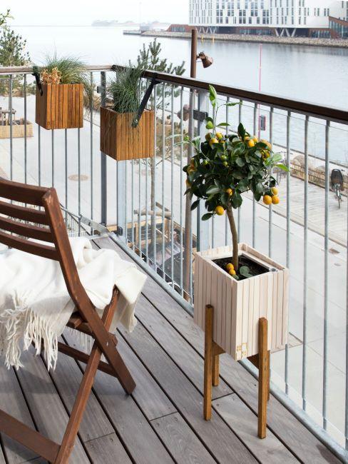 balcon avec jardinieres et chaise avec plaid pose dessus