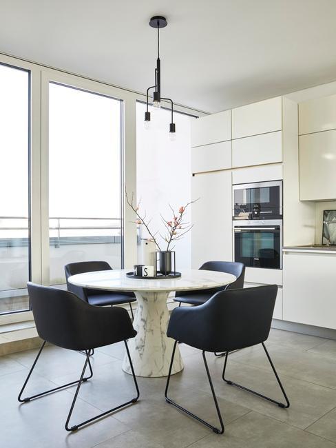Salon de style moderne avec une table ronde autour de laquelle se trouvent 4 fauteuils en cuir bleu foncé