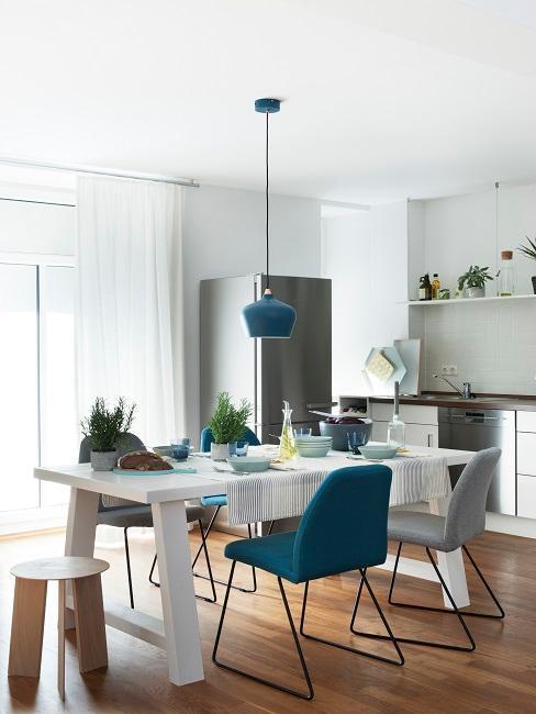Salle à manger avec table blanche et suspension bleue