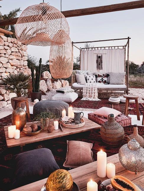 Coin oriental à l'extérieur avec bougies, coussins; poufs, déco en rotin et table en bois massif