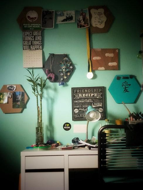 mur vert avec différents cadres et objets décoratifs accrochés dessus