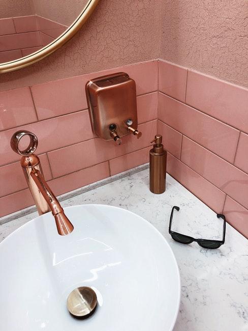 Salle de bain à carrelage rose et accessoires cuivrés